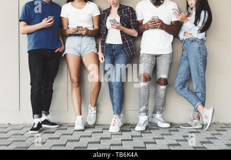 Always connected people on modern mobile phones. Group of teenagers using cellphones outdoor, free space - Stock Photo