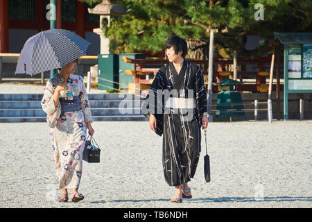 A Japanese tourist couple dressed in traditional kimono yukata look at each other in Heian Jingu Shrine's courtyard. The woman holds an umbrella. - Stock Photo