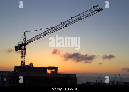 Silhouette of a construction crane against the sunset in Antofagasta, Chile - Stock Photo