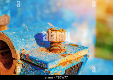 Rusty metal bolts and nuts on metal mounts. Abandoned equipment. - Stock Photo