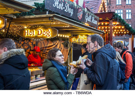 Visitors at fastfood stand eating hot dogs at Christmas market during Xmas festivities in winter - Stock Photo