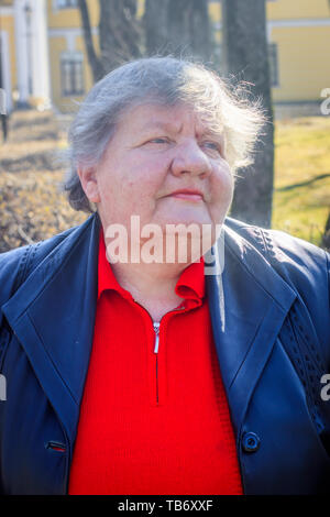 Elderly woman on a bench in the city. Grandmother in a red sweater and leather jacket. old woman - Stock Photo