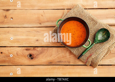 lentil soup in a soup plate on a canvas on a wooden background. top view - Stock Photo