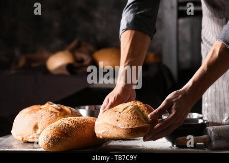 Young man with freshly baked bread in kitchen - Stock Photo