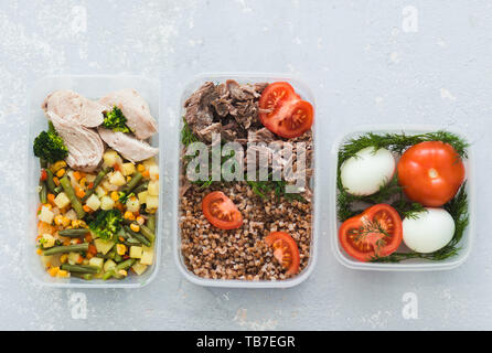 Diet food in the three containers on a gray background. Boiled and fresh vegetables, buckwheat, eggs, beef, chicken. top view - Stock Photo