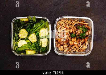Flat lay of two containers with vegetables and mushrooms on a black wooden background, closeup. Healthy diet, good nutrition concepts. - Stock Photo