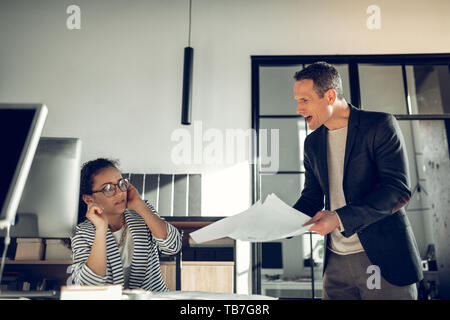 Mature boss shouting at his young trainee for not finishing task - Stock Photo