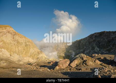 Rock formations and fumaroles on the volcanic island of White Island with rising steam from the crater, Whakaari, Volcanic Island, Bay of Plenty - Stock Photo
