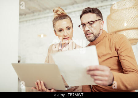 Checking sketches. Two motivated designers looking attentively at their sketches for new collection holding laptop and sheet of paper. - Stock Photo