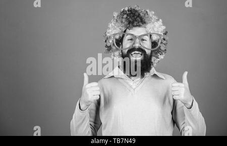Dressed up for birthday party. Man in fashion wig gesturing thumbs up. Bearded man in clown wig hairstyle. Hipster man wearing rainbow wig hair. Happy man with long beard and curl wig, copy space. - Stock Photo