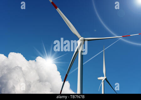 Two wind turbines on a blue sky with clouds and sun rays - Renewable energy concept