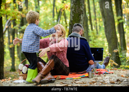 Conflicts of being dad. Family and career goals. Dad is always busy. Family day concept. Family with kid boy relaxing in forest. Mother and little play together while father working with laptop.
