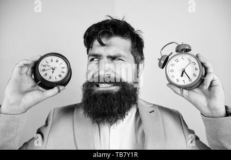 Does changing clock mess with your health. Man bearded hipster hold two different clocks. Guy unshaven puzzled face having problems with changing time. Time zone. Changing time zones affect health. - Stock Photo