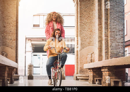 Happy couple going on bicycle in the city center - Young people having fun outdoor - Millennial generation and youth lifestyle concept - Stock Photo