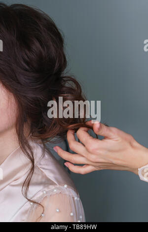 Hairdresser at work in process of creating wedding hairstyle. Hand hairdresser straightens brown curls. Perfect and beauty in details. Beauty industry - Stock Photo