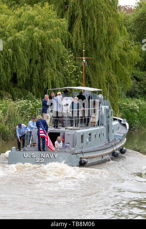 The P22, former US built Rhine River Patrol Boat, leaves Sandwich with a select crew on the first stage of a journey to France for the 75th anniversary of D-Day in June 2019. Stern of patrol boat as it cruises down river past trees. US flag flying from stern, several people standing on decks. - Stock Photo