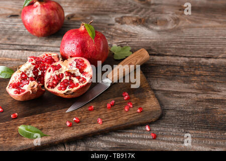 Cutting board with ripe pomegranates and knife on wooden table - Stock Photo