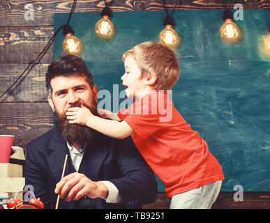Childhood concept. Father painting while son is distracting him. Little kid holding his hand over daddy s mouth.