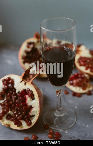 Red wine with an open pomegranate on a textured gray concrete background. Pomegranate seeds on a gray grunge background. The concept of expensive deli - Stock Photo