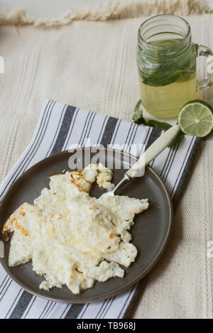 Delicious cooked omelet on a gray napkin and beige carpet. Homemade lemonade and scrambled eggs for breakfast. Dark dishes on a light background. - Stock Photo