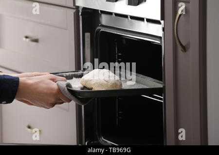Woman putting baking tray with raw dough for bread into oven - Stock Photo