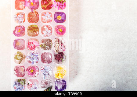 Tray with Frozen Flowers in Ice Cubes on grey Background, top view, copy space for text - Stock Photo