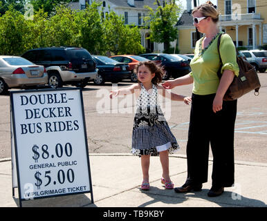 A child points to a double-decker tour bus as she waits for a ride with her mother in Columbus, Mississippi. - Stock Photo