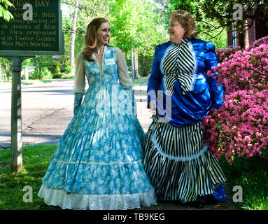 Women in antebellum dresses stroll past Twelve Gables in Columbus, Mississippi, April 16, 2010. - Stock Photo