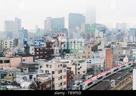 Tokyo, Japan - March 30, 2019: Shinjuku cityscape view buildings on cloudy grey mist fog overcast day with many houses and red metro train with tracks - Stock Photo