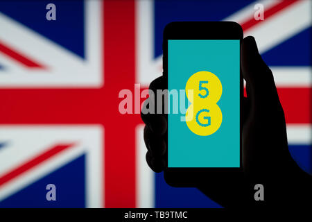 A silhouetted hand of a man holds a smartphone displaying the logo of EE  5G, infront of a UK flag (Editorial use only). - Stock Photo
