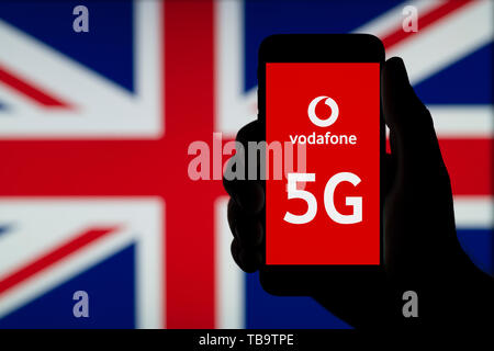 A silhouetted hand of a man holds a smartphone displaying the logo of Vodafone and the letters 5G, infront of a UK flag (Editorial use only). - Stock Photo