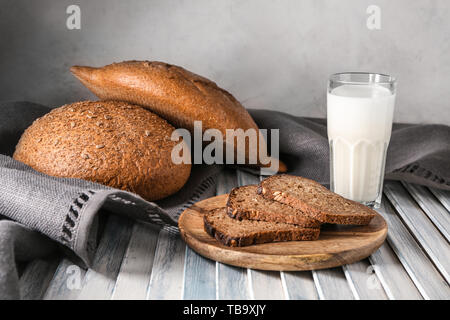 Tasty fresh bread with milk on wooden table - Stock Photo