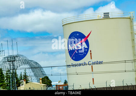 The Nasa logo on a storage tank and the dirigible  hangar under restoration at Moffett Field in the Silicon Valley of California now owned by Google - Stock Photo