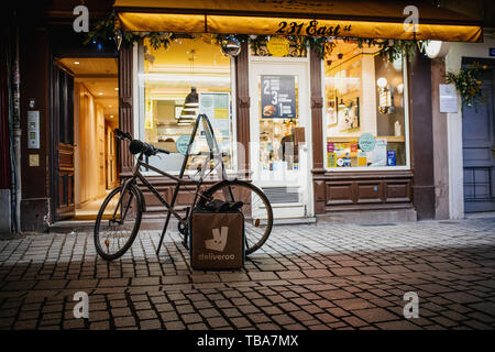 Strasbourg, France - Dec 27, 2017: Street view at night of parked bicycle in front of restaurant and Deliveroo carrying thermo box near the bike 231 East burger restaurant food delivery - Stock Photo