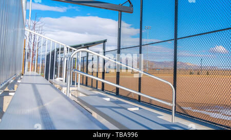 frame Panorama Sunlit bleachers overlooking a vast sports field on the other side of the fence - Stock Photo