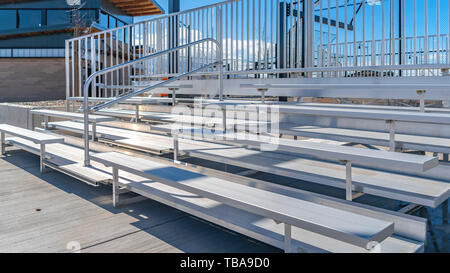 frame Panorama Bleachers with railings against a building and cloudy blue sky - Stock Photo