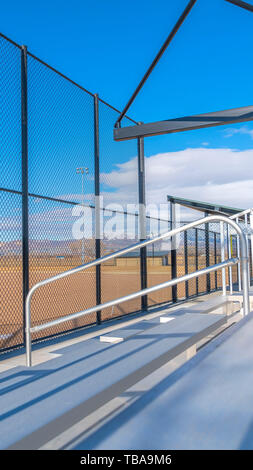 frame Vertical frame Sunlit bleachers overlooking a vast sports field on the other side of the fence - Stock Photo