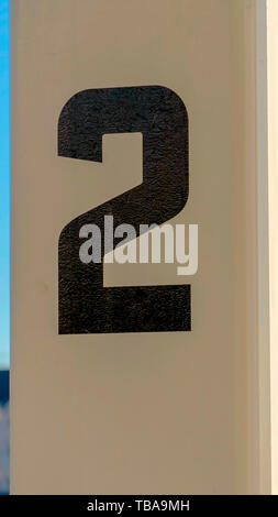 frame Vertical frame Close up of white rectangular posts with numbers painted on the surface - Stock Photo