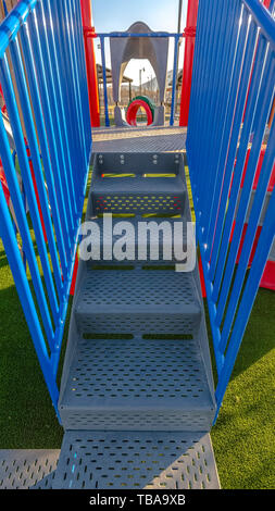 frame Vertical Stairs going up a slide overlooking mountain and bright sky on a sunny day - Stock Photo