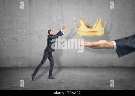 Side view of little businessman reaching out for gold crown that is levitated above big man's hand emerging from right. - Stock Photo
