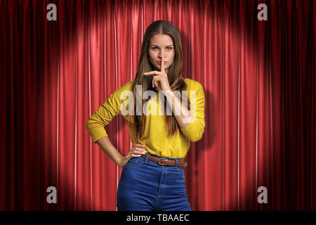 Front crop view of pretty woman standing in spotlight at red stage curtain, one hand on hip, other hand doing silencing gesture with index finger at - Stock Photo