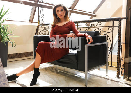 Stylish young lady sitting on the black sofa in a hall. Wearing long red dress and black shoes with high heel shoes. Shooting indoor for the fashion - Stock Photo