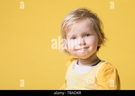 Young Blonde Girl in Yellow Dress Cheerfully Laughing, Smiling and Having Fun on Yellow Background - Stock Photo