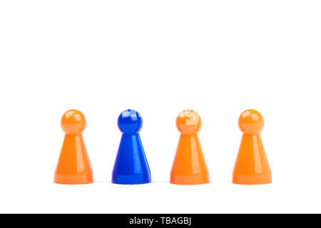 A series of orange game pieces and one different and exceptional blue figure as leader or boss - isolated on a white background