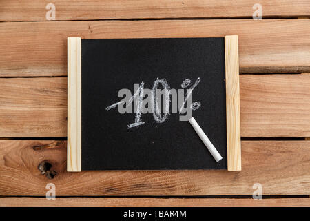 chalk Board with the inscription -10 percent on a wooden background. the view from the top - Stock Photo