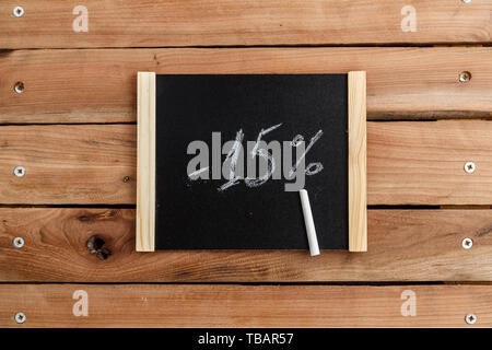 chalk Board with the inscription -15 percent on a wooden background. the view from the top - Stock Photo