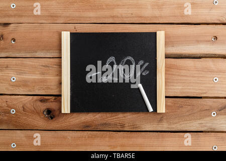 chalk Board with the inscription -20 percent on a wooden background. the view from the top - Stock Photo