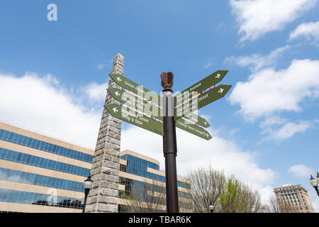 Asheville, USA - April 19, 2018: Downtown old town street in hipster North Carolina NC famous town with sign on intersection for direction to landmark - Stock Photo