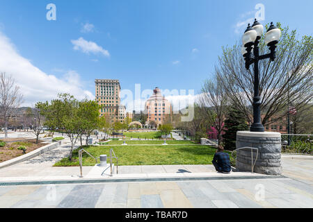 Asheville, USA - April 19, 2018: Man sitting looking at buildings courthouse and green Pack Square Park in hipster North Carolina NC famous town city  - Stock Photo