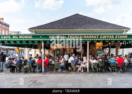 New Orleans, USA - April 22, 2018: People sitting at tables at iconic Cafe Du Monde restaurant sign eating beignet powdered sugar donuts and chicory c - Stock Photo